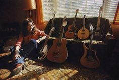 Rory Gallagher posing with his guitars