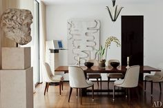 In Waldo Fernandez's L.A. dining room, an Albert Cheuret light fixture is suspended over a 1930s André Sornay table. The wall sculpture is by Thomas Houseago.