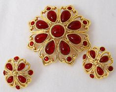 """Signed Trifari brooch earring Parure red rhinestones gold tone metal flower -  Etsy & Ebay - A lovely demi - parure consisting of a pair of clip-on earrings and a brooch.  Each item has burgundy red  cabochon rhinestones in a gold tone setting.  The brooch has 8 teardrop cabochons and 8 round ones. The earrings have 4 teardrop cabochons and 4 round ones.  The brooch is approximately 2 1/4"""" across. The earrings are approximately 1"""" across.  There is always a place for """"RED"""" in your wardrobe!"""