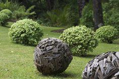 Teak lawn balls mirroring the Pittosporum 'Golf Ball' at Omaio garden, Matakana