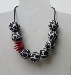 Emma Necklace by Klara Borbas. Lightweight polymer beads on black rubber cord with stainless steel clasp. The black and white beads are spiced up with a red accent.