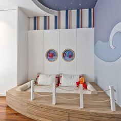 O quarto infantil desta casa em Curitiba tem como tema o mar. A cama baixa com proteção lateral leva cordinhas remetendo ao desenho de um navio.  Molduras redondas com desenho de escotilhas com bichinhos do mar foram aplicadas no painel da cabeceira e nas portas dos armários.  Projeto: @spstudio_arq  📷: Marcelo Stammer #revistacasaclaudia #decor #decoration #decoração #home #house #casa #homedecor