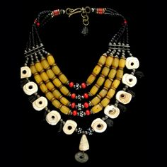 by Milene Rust | Old well worn Mauritanian conus shells, small Dogon shell pendant, old West African coin, Copal amber from Ethiopia, red Dogon glass beads from West African Trade, 18th cen. glass Eye beads, black tube glass beads from Turkana Tribe from Kenia. Vintage brass spacers from Eastern Cape, South African(Xhosa tribe).