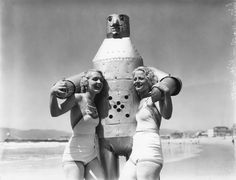 Two bathers and their robotic friend mug for the camera, Venice Beach, California, 1930's.