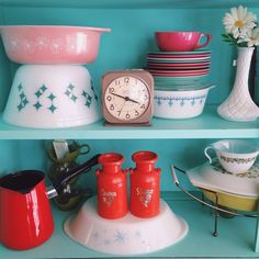 Pyrex and vintage kitchen knick knacks on turquoise shelves.