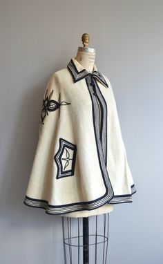 Vintage 1960s pale flax wool cape/poncho with black embroidery, turned down collar and one closure at the neck. --- M E A S U R E M E N T S ---  fits like: fits most shoulder: n/a bust: free length: 28 brand/maker: n/a condition: excellent  ★ layaway is available for this item  ➸ More vintage coats http://www.etsy.com/shop/DearGolden?section_id=5800175  ➸ Visit the shop http://www.DearGolden.etsy.com _____________________  ➸ instagram | d...