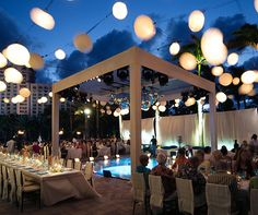 String lighting gives the illusion of dining and dancing under a starry night sky for this outdoor wedding.