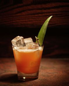 1 1/2 oz. aged rum 1 1/2 oz. fresh pineapple juice 3/4 oz. spicy ginger syrup 1/2 oz. fresh lemon juice 1 dash each Angostura and Peychaud's bitters Tools: shaker, strainer Glass: Old Fashioned Garnish: skewered sour cherry and a pineapple leaf (optional)