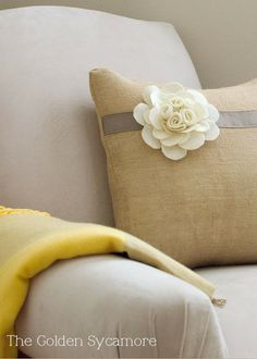 Embellished Burlap Pillow DIY Tutorial - The Golden Sycamore. She gives step by step pics on how to sew this and make the felt flower.