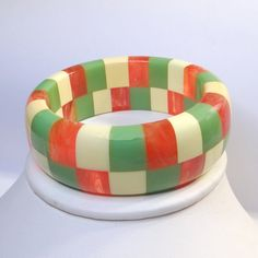 A blast from the past, this plastic bangle is a checkerboard of cream, green and marbled applejuice. Signed Shultz on the inside across a green and