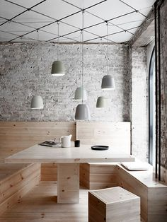 Love the composition of textures: black frame window, white stain brick wall, paper whites glossy pendants and light wood