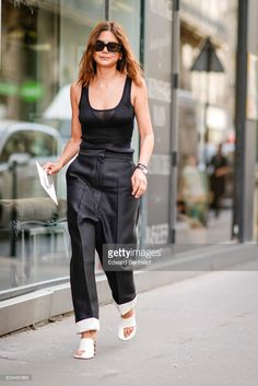 Christine Centenera wears sunglasses, a black low-neck tank top, black pants, white shoes, outside the Valentino show, during Paris Fashion Week - Haute Couture Fall/Winter 2017-2018, on July 5, 2017 in Paris, France.