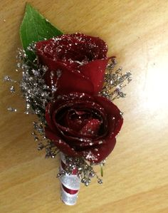 Dark red/burgundy spray rose boutonniere accented in silver glitter gyp and stem wrapped in both colors.