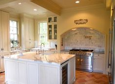 Traditional kitchen design with terracotta floors, marble counters and backsplash, warm white walls and cabinets.