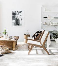 Swedish living space with wooden midcentury modern armchairs, black and white photography, and a vintage coffee table