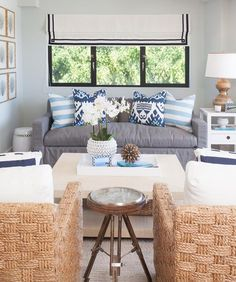Gray and blue cottage living room features a gray slipcovered skirted sofa lined with turquoise striped pillows and blue ikat pillows flanked by a sea fan art gallery to the left and a white end table, Bungalow 5 Polo 1 Drawer Side Table, to the right placed under windows dressed in a black and white Greek key roman shade.