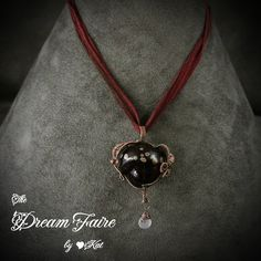 """""""Forbidden Fruit"""" Artisan Hollow Glass Bead in Wire Woven Copper Burgundy wine colors blend into a rich, jewel-toned backdrop for metallic raku drops that resemble the seeds of the forbidden fruit, the apple."""