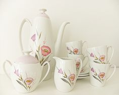 4 cups and saucers together with coffee pot /tea pot, milk jug and sugar bowl.
