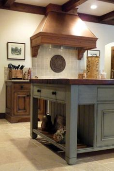 See more of my French Gray Island Kitchen at Atticmag.com Custom copper range hood. Custom island with open end shelving. Gorgeous color.