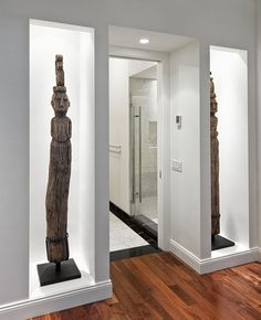 Recessed wall niches display and protect two antique, hand-carved sculptures.