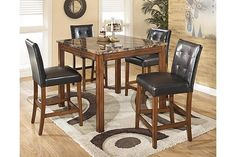 "The Theo Counter Height Dining Room Table and Barstools (Set of 5) from Ashley Furniture HomeStore (AFHS.com). The rich contemporary style of the ""Theo"" Counter Height Table combines faux marble and a warm finish to create dining room furniture that adds an exciting style to the decor of any home."