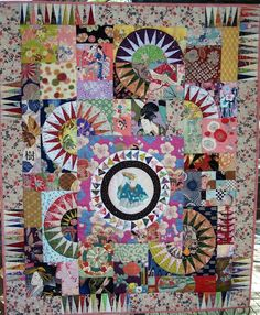 """Emperor's Wheel, 50 x 61"""", by Chris Jurd at PatchworkFun      Chris Jurd's """"Emperor's Wheel"""" features a recycled kimono center surrounded by curved foundation pieced flying geese. Lots of oriental prints are combined with foundation pieced New York Beauty blocks to create this stunning quilt.  We love the mixture of New York Beauty blocks with focus fabrics!"""