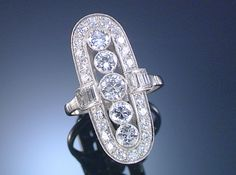 DIAMOND RING, 1930S Designed as an elongated oval open work plaque, collet-set at the centre with five principal circular-cut diamonds, within borders of millegrain-set baguette and circular-cut diamonds