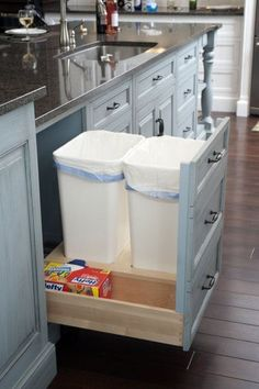 A cabinet with built-in spots for trash, recyling, and trash bags.