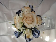 Gold tipped spray roses for a wrist corsage. Perfect for a blue and gold dress for Prom. Gold pearls and blue and gold ribbon.  expressions24-7.com