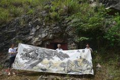 Chinese cave-living artist Song Chuanzhong displays one of his paintings in front of his cave studio  Other Chinese who choose to live in caves: http://viewofchina.com/modern-chinese-hermits/