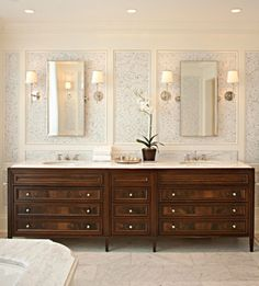 Dark wood to match bedroom furniture. Alternate look to white bathroom.  Beautiful trim work with /mini mosaic tile on walls with hint of color.  Sconces with separate mirrors.  Marble floors.  Tailored and beautiful.