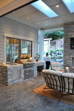 Outdoor kitchen. Grey stone. Don't like the grill in front of the window