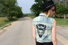 """Beautiful denim vest featuring a large buffalo head painted on back. Black studs adorn side pockets and collar.    Size XS/SM    Vest is was distressed, bleached, stenciled and studded by hand.     Shoulder to Shoulder: 13""""  Length: 19""""  Waist: 15 1/2"""""""