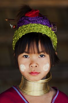 A young girl from the Padaung hill tribe aka long neck, a sub-group of the Karen hill tribe, near Chiang Mai in Northern Thailand, stares intensely at the camera. The Padaung are Burmese refugees that fled to Thailand in order to escape persecution. The brass rings around their necks are considered to be a sign of great beauty.