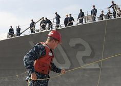 Mineman Seaman Patrick J. Bruce, assigned to Navy Munitions Command CONUS West Division, Unit Seal Beach, Underwater Weapons Department, hauls in a line as the guided-missile destroyer USS Sampson (DDG 102) arrives at Naval Weapons Station Seal Beach to conduct ordnance operations. (U.S. Navy photo by Mass Communications Specialist 1st Class Eli J. Medellin/Released)