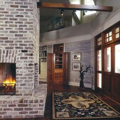 whitewashed brick fireplace, dark wood floor and lighter/washed wood accent wall