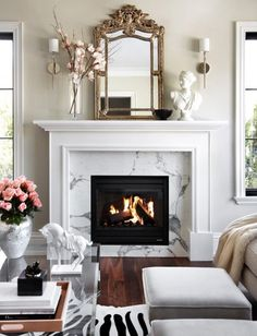 Marble #fireplace surround and wooden white #mantel with lucite table and zebra rug