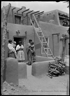 Tewa women and children in front of home, San Juan Pueblo (Ohkay Owingeh), New Mexico Photographer: T. Harmon ParkhurstDate: 1915 - 1920?Negative Number 043064