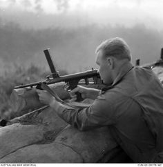 Aiming his Owen machine carbine from his fox hole, during a dawn stand to is Private Rudolph V Ascuks, of Woolongong, NSW, 3rd Battalion, The Royal Australian Regiment (3RAR).