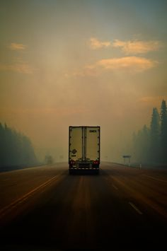 A lonely truck makes it's way down the road, early on a foggy morning.