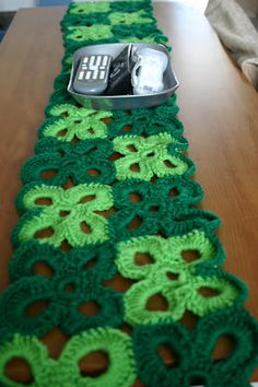 The table runner was inspired by the free Red Heart Four Leaf Clover Afghan pattern. Use two bright shades of green, sew them together, and single crochet a border around all.
