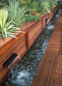 What a great idea for a deck!  This small fountain adds a touch of elegance and the plant selection and mini waterfalls give it a tropical feel.