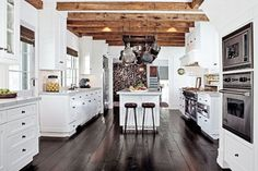In the kitchen, Gallin installed reclaimed-timber beams and lined the floor in dark-wood planks, another of his signatures.