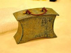 Lidded Vessel with found objects and wrapped copper handle<br />High Fired<br />