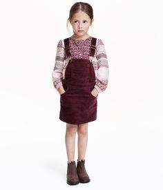 Burgundy. Bib overall dress in corduroy with adjustable suspenders. Bib pocket, front and back pockets, and snap fasteners at sides. Lined at top.