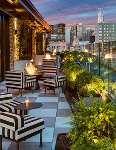 On the rooftop's outdoor patio, the bold black and white striped chairs hold their own against the sparkling San Francisco skyline. | Photographer: Courtesy of San Francisco Proper | Designer: Kelly Wearstler