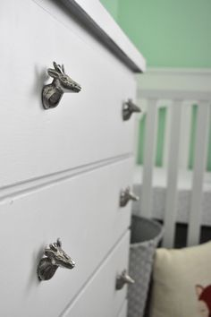 woodland theme nursery: love the Deer dresser knobs from hobby lobby, fox pillow, and mint walls, so cute! The grey dresser looks so good with everything else in this baby nursery. Adorable.
