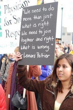 """Woman holding sign that reads: """"We need to do more than just what is right. We need to join together and right what is wrong."""" Leonard Pellitier"""