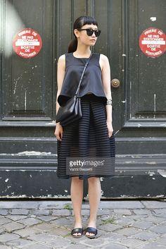 Val Tseng poses wearing a Maje skirt and Celine bag after the Lanvin show at the Ecole des Beaux Arts de Paris on June 28, 2015 in Paris, France.