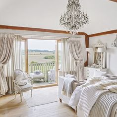 Main bedroomThe wow factor was added to the main bedroom with the installation of a balcony. 'We live in a conservation area so we couldn't put lots of windows in, but we installed French doors with large oak framed windows on either side.' To keep the look light and bright, an off-white palette was introduced and elegance injected with French-style furniture and a huge chandelier that enhances the vaulted ceiling. 'I love neutral palettes and antiques but the house only lends itself to a…